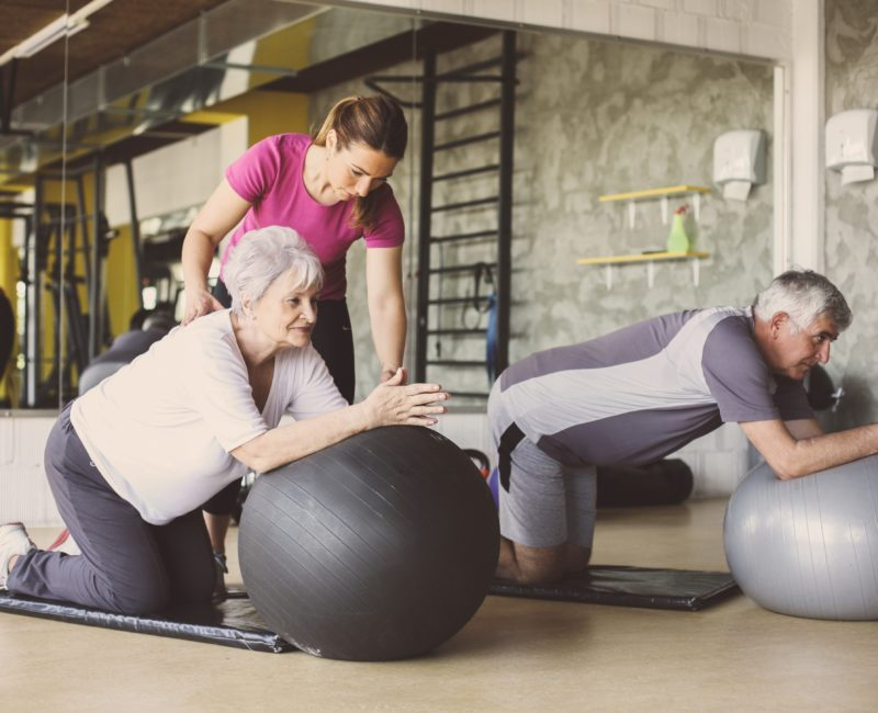 Senior people workout in rehabilitation center. Personal trainer helping senior people on Pilates ball.